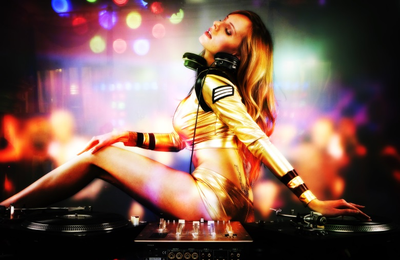 Beautiful DJ girl on decks playing on the party people on the dancefloor